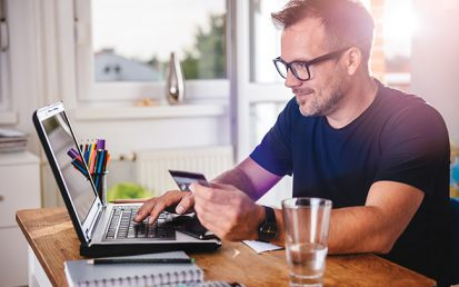 Businessman using credit card and laptop at home office